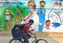 A cyclist rides past a mural honouring Covid warriors, in New Delhi   PTI