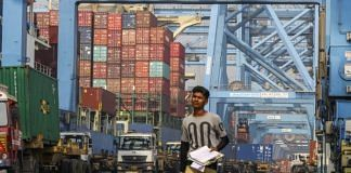 An employee walks past gantry cranes loading shipping containers onto trucks from the Cosco New York container ship docked at the Jawaharlal Nehru Port, operated by JNPT, in Navi Mumbai. Photographer: Dhiraj Singh | Bloomberg