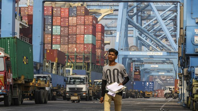 An employee walks past gantry cranes loading shipping containers onto trucks from the Cosco New York container ship docked at the Jawaharlal Nehru Port, operated by JNPT, in Navi Mumbai. Photographer: Dhiraj Singh   Bloomberg