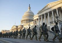 Members of the National Guard walk outside of the U.S. Capitol building in Washington, D.C., U.S., on Wednesday, Jan. 13, 2021. | Bloomberg