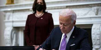 US President Joe Biden signs an executive order after speaking during an event on his administration's Covid-19 response as Vice President Kamala Harris looks on. | Photographer: Al Drago | Bloomberg