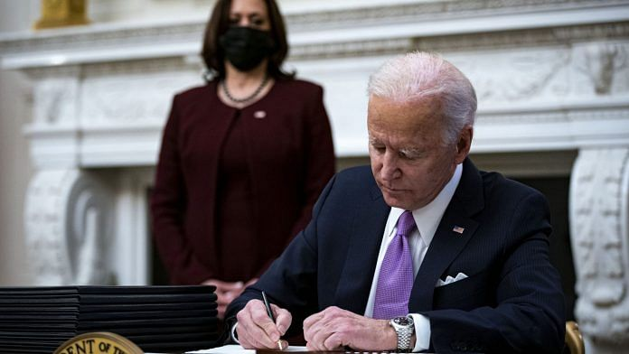 US President Joe Biden signs an executive order after speaking during an event on his administration's Covid-19 response as Vice President Kamala Harris looks on.   Photographer: Al Drago   Bloomberg