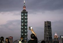 People take photographs of the Taipei 101 building and other buildings illuminated at dusk in Taipei (Representational photo) | Photographer: I-Hwa Cheng | Bloomberg