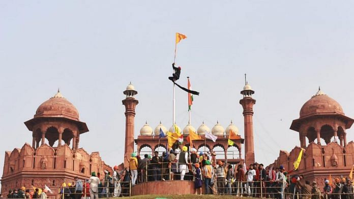 A protester hoists the Nishan Sahib at the Red Fort in Delhi on 26 January | ThePrint Photo | Manisha Mondal