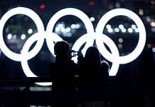 A visitor takes a photograph of illuminated Olympic rings floating in the waters off Odaiba island in Tokyo, Japan on 14 January | Photo: Toru Hanai | Bloomberg