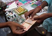 A vendor hands Indian rupee notes to a customer at a stall in Chauta Bazaar in Surat, Gujarat (representational image) | Photo: Karen Dias | Bloomberg