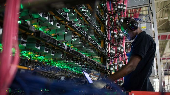 A technician monitors cryptocurrency mining rigs at a Bitfarms facility in Saint-Hyacinthe, Quebec, Canada | Representational image