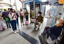 A health worker in protective gear collects a swab sample from a passenger at Nizamuddin Railway Station in New Delhi