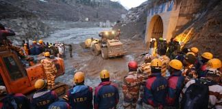 Rescue and relief workers stand near the damaged Rishi Ganga power project | Photo: Suraj Singh Bisht | ThePrint