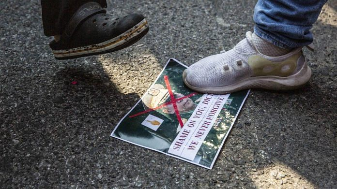 A demonstrator steps on an image of Army chief Min Aung Hlaing during a protest outside Myanmar Embassy in Bangkok, Thailand, on 1 Feb 2021