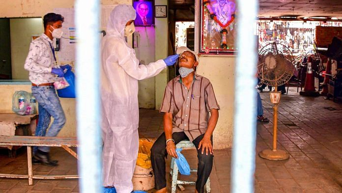 A heath worker, wearing PPE, conducts COVID-19 testing of a man at Dadar market in Mumbai on 22 March, 2021 | PTI