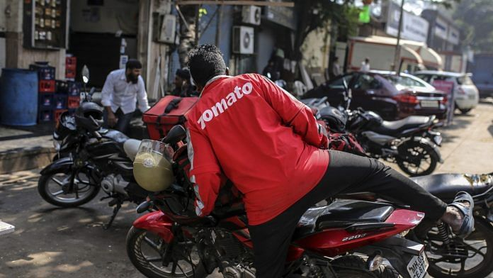 A food delivery rider for Zomato Media Pvt. gets on a motorcycle as he waits for an order outside of a restaurant in Mumbai, India, on Tuesday, Jan 21, 2020. Uber Technologies Inc. will sell Uber Eats in India to local rival Zomato in a $172 million deal, according to a person familiar with the transaction, underscoring the ride-hailing giant's effort to cut back on loss-making operations. Photographer: Dhiraj Singh/Bloomberg