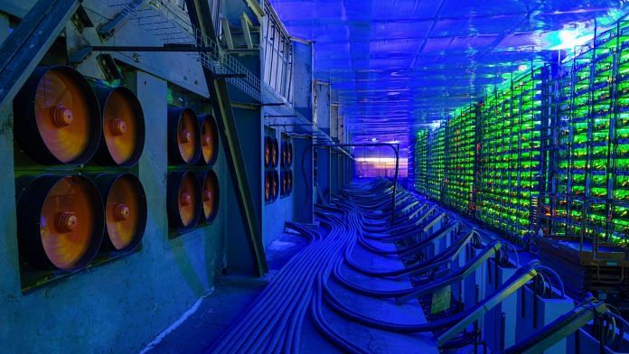 Industrial cooling fans operate to thermally regulate illuminated mining rigs at the CryptoUniverse cryptocurrency mining farm in Nadvoitsy, Russia   Representational Image   Photographer: Andrey Rudakov   Bloomberg