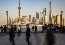 File photo | Visitors walk on the Bund in Shanghai, China | Qilai Shen/Bloomberg