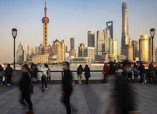 File photo | Visitors walk on the Bund in Shanghai, China | Qilai Shen/Bloomberg