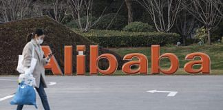 A pedestrian passes by a logo outside the Alibaba Group Holding Ltd. headquarters in Hangzhou, China