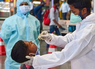 A health worker takes a nasal swab sample of a passenger for coronavirus tests at the CSMT railway station, owing to surge in COVID-19 cases in Mumbai, Friday, Feb. 26, 2021. | PTI