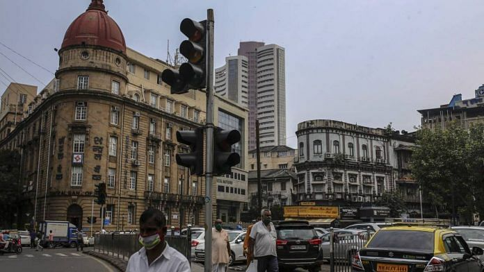 Pedestrians wearing protective masks walk past an out of service traffic signal as the Bombay Stock Exchange (BSE) building stands in the background in Mumbai on 12 October 2020 | Dhiraj Singh | Bloomberg