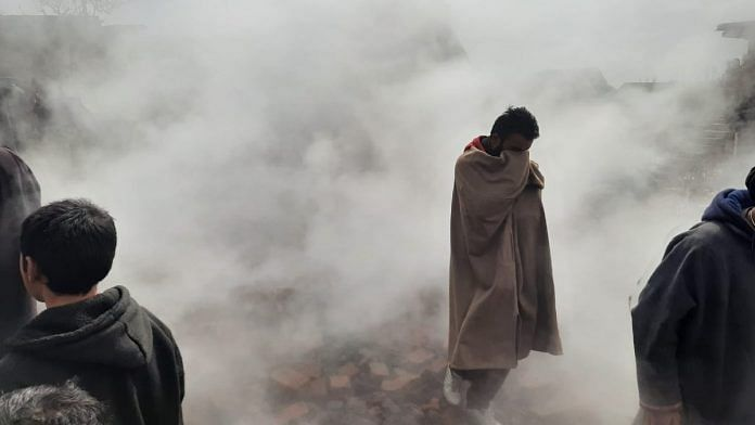 A Rawalpora resident stands amid smoke from the gutted remains of some local homes | Azaan Javaid | ThePrint