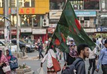 A street vendor carries Bangladeshi national flags in Dhaka, Bangladesh
