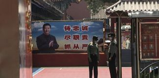 People's Liberation Army soldiers in front of a banner depicting Chinese president Xi Jinping near the Forbidden City in Beijing | Photo: Qilai Shen | Bloomberg File
