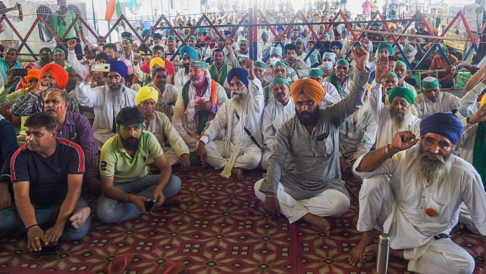 Farmers raise slogans during their ongoing protest against the new farm laws, at Ghazipur border in New Delhi on 29 March 29, 2021 | PTI