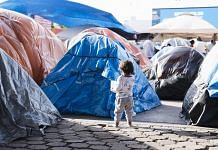 A child walks past tents at a makeshift housing camp for migrants seeking asylum hearings in Tijuana, Mexico | Photographer: Eric Thayer | Bloomberg