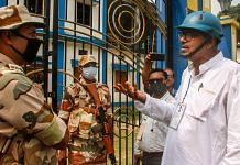 TMC candidate Rabindra Nath Ghosh, wearing a helmet for safety, interacts with security personnel during 4th phase of West Bengal polls, in Cooch Behar | PTI