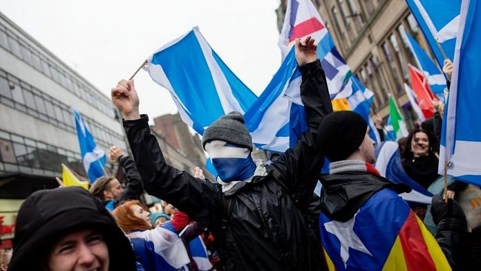 A demonstrator holds a Scottish national flag while marching during an All Under One Banner (AUOB) march for Scottish independence in Glasgow, Scotland on Saturday, Jan. 11, 2020. | Photographer: Emily Macinnes | Bloomberg