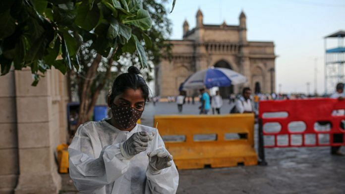 A healthcare worker prepares to administer a rapid antigen test near the Gateway of India monument in Mumbai | Photographer: Dhiraj Singh | Bloomberg