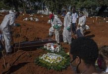 Mourners watch as workers wearing protective equipment bury the casket of a Covid-19 victim at the Vila Formosa cemetery in Sao Paulo, Brazil | Bloomberg