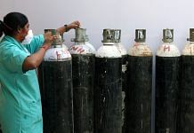 A health worker check oxygen cylinders at a makeshift Covid-19 quarantine facility set up in a banquet hall in New Delhi | Bloomberg