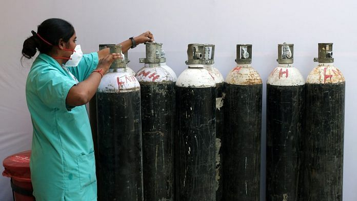 A health worker checks oxygen cylinders at a makeshift Covid-19 quarantine facility set up in a banquet hall in New Delhi | Representational image | Bloomberg