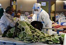 A health workers in personal protective equipment (PPE) assists a patient at a makeshift Covid-19 quarantine facility set up in a banquet hall in New Delhi | Bloomberg