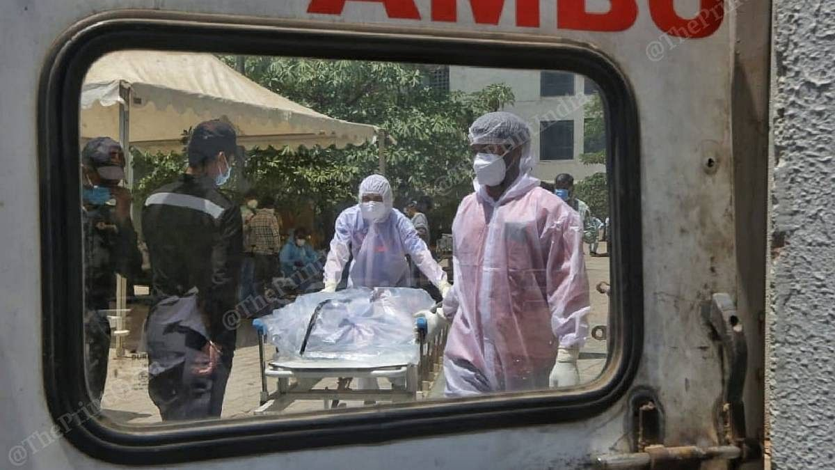 Hospital workers move a dead Covid patient, to be transported to a crematorium | Praveen Jain | ThePrint