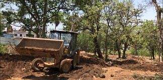 A JCB digs the ground for a grave at Bhopal's Jahangirabad graveyard | Taran Deol | ThePrint