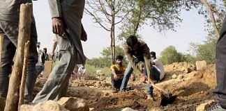Staff at Delhi's Qabristan Ahle Islam dig a grave for a Covid patient Thursday | Tenzin Zompa | ThePrint
