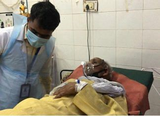 A doctor attends to Covid patient Bamau Ram Kannojia, 70, at Jaunpur district hospital | Jyoti Yadav | ThePrint