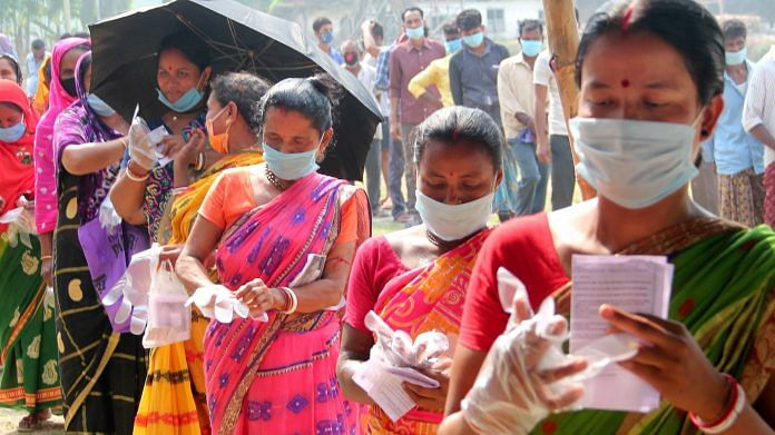 Voters wait in queues to cast votes at a polling station during the 7th phase of West Bengal Assembly elections at a village near Balurghat in South Dinajpur district on Monday, April 26, 2021.   PTI