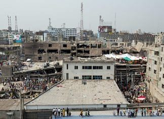 People stand and watch as rescue workers search for victims amongst the debris of the collapsed Rana Plaza building in Dhaka, Bangladesh, on 26 April 2013 | Photo: Jeff Holt | Bloomberg