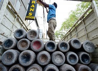 Workers load empty cylinders of medical oxygen in New Delhi, 21 April 2021 | PTI Photo