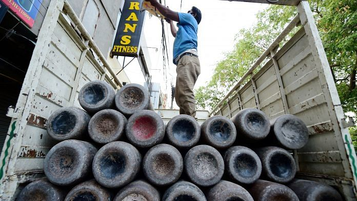 A worker loads empty cylinders of medical oxygen in New Delhi, on 21 April 2021 | PTI