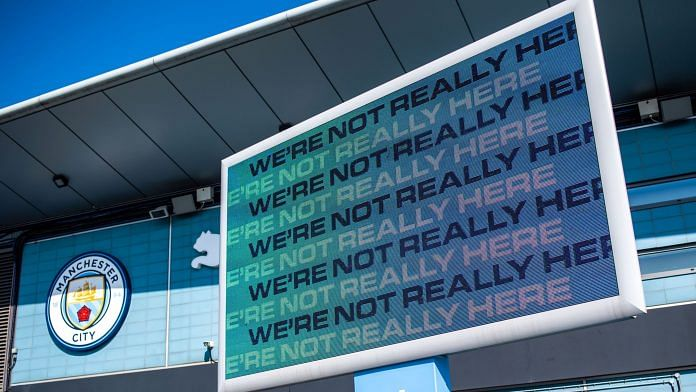 A sign reading 'We're Not Really Here' on display outside the City of Manchester Stadium, also known as the Eithad Stadium, the home ground of Manchester City Football Club, in Manchester on 19 April 2021