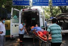 A covid patient being shifted from one ambulance to another after the oxygen in the cylinder got over, outside LNJP Hospital in New Delhi | Suraj Singh Bisht | ThePrint