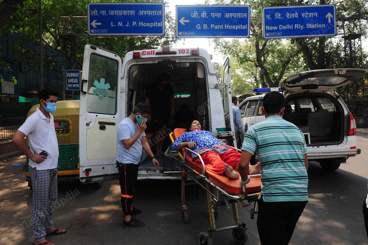 A covid patient was being shifted from one ambulance to another as the oxygen in the cylinder finishes in the ambulance outside LNJP   Suraj Singh Bisht   ThePrint