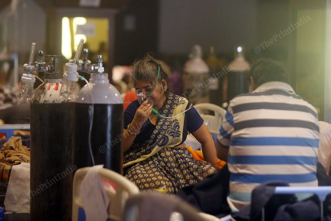 At Shehnai banquet an old woman uses oxygen cylinder to breathe. The family members of patients were quite happy with the facility, they said the doctors are taking good care   Suraj Singh Bisht   ThePrint