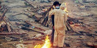 Family members stand between burning pyres at the Seemapuri crematorium | Praveen Jain | ThePrint
