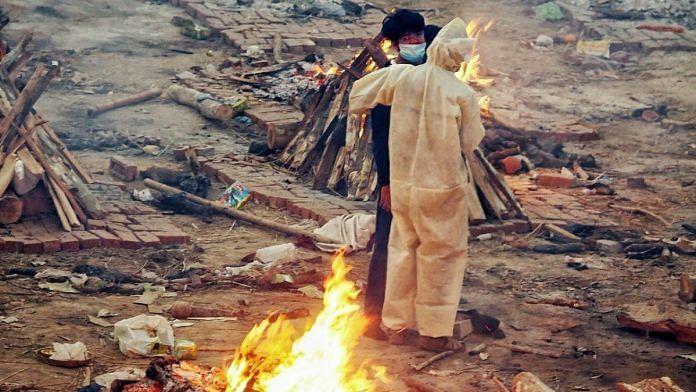 Family members stand between burning pyres at the Seemapuri crematorium   Praveen Jain   ThePrint