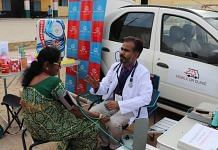 Dr Sunil Kumar Hebbi with a patient next to his 'mobile clinic' in pre-Covid times | Photo: Facebook | Sunil Kumar Hebbi