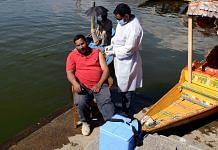 A medic administers the Covid-19 vaccine beside a shikara at the Dal Lake in Srinagar | Photo: ANI
